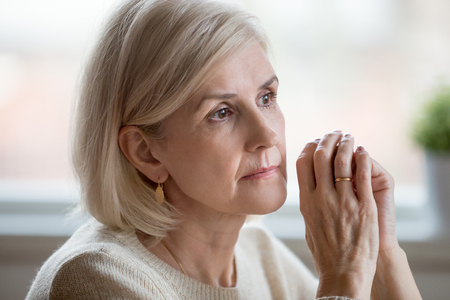 Foto per Close up portrait of beautiful sad woman folding hands together near her face, thinking about life. Aging is period of physical decline and senile dementia, mental disorders emotional problems concept - Immagine Royalty Free
