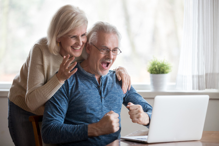 Foto de Happy aged spouses looking on pc screen feels happy received unbelievable great news, enjoying celebrating win online lottery. Senior positive wife husband founding out about sale and huge discounts - Imagen libre de derechos