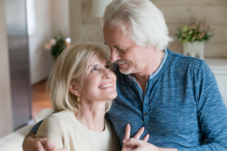Photo pour Wife and husband in casual clothes at home, grey old man cuddling blonde middle aged woman with charming shiny white smile, people looking at each other with love tenderness and passionate, close up - image libre de droit