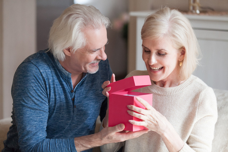 Foto de Spouses celebrating special occasion, grey haired husband giving to loving pretty happy wife pink gift box with long awaited present, she feels excited and satisfied. Making joy to loved ones concept - Imagen libre de derechos