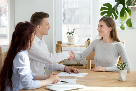 Foto de Smiling friendly hr manager handshake applicant welcoming at job interview or hiring successful candidate, satisfied recruiter female seeker shaking hands at meeting, recruitment employment concept - Imagen libre de derechos