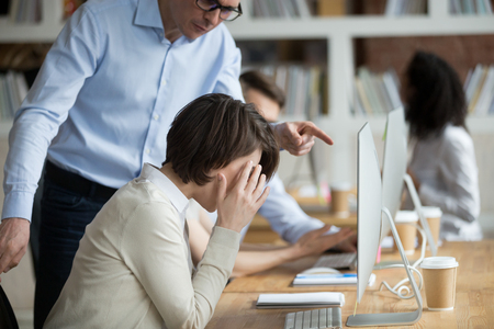Foto de Stressed employee intern suffering from gender discrimination or unfair criticism of angry male boss shouting scolding firing female worker for bad work, computer mistake or incompetence in office - Imagen libre de derechos