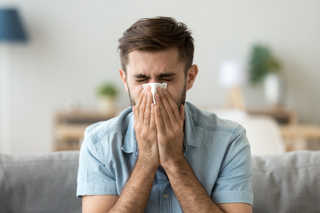 Ill young man sneezing in handkerchief blowing wiping running nose, sick allergic guy caught cold got flu influenza hay fever coughing, having seasonal allergy symptoms respiratory contagious disease