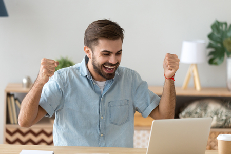 Photo pour Euphoric young man celebrating success victory excited by online bet bid win at home looking at laptop, happy male winner feel lucky successful got new job opportunity, received good exam test result - image libre de droit