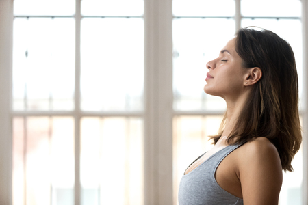 Photo for Focused young beautiful sporty woman in sportswear with eyes closed training in fitness studio, calm fit millennial female practice yoga, help control emotions and balance stress. Healthy life concept - Royalty Free Image