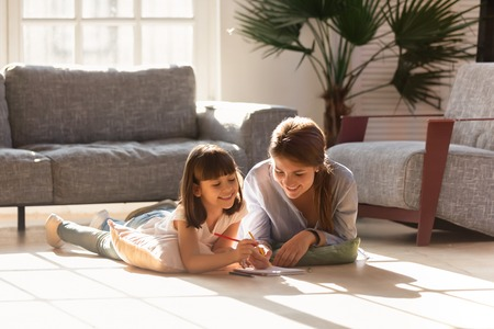 Foto de Happy mom helping child daughter drawing with colored pencils laying on warm floor together, smiling baby sitter mother teaching cute kid learning creative activity play laugh at home in living room - Imagen libre de derechos