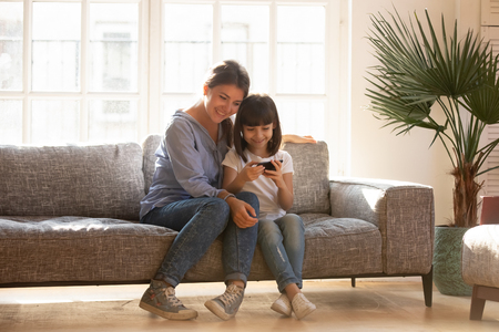 Photo pour Happy mom and little kid daughter enjoy using mobile apps on smartphone sitting on couch, smiling mother and cute child girl play on phone gadget have fun together with cellphone at home on sunny day - image libre de droit