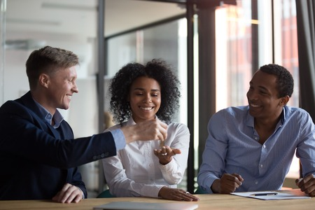 Photo pour Three diverse people gathered in real estate agency, signing lease agreement afro woman receiving keys from first dwelling new home, giving keys to female client after making a property deal - image libre de droit