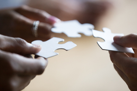 Foto de Close up hands of african american and caucasian associates multinational teammates holding white pieces of puzzle, people searching and finding solution. Team building, teamwork and support concept - Imagen libre de derechos