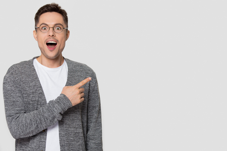Foto de Amazed funny man in glasses pointing finger aside at copy space excited by unbelievable offer looking at camera, surprised male customer advertise product service isolated on studio blank background - Imagen libre de derechos