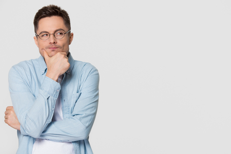Photo pour Thoughtful suspicious young man looking aside at copy space feeling skeptic doubtful, distrustful sly cunning guy thinking holding hand on chin isolated on grey white studio background - image libre de droit