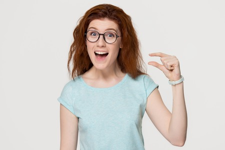 Photo for Funny excited redhead woman showing something very tiny little size by fingers, happy red-haired girl with open mouth amazed by small prices looking at camera isolated on white grey studio background - Royalty Free Image
