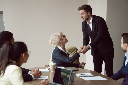 Photo pour Satisfied grateful partner employee holding shaking hand of executive thanking for help or opportunity, expressing respect and gratitude at team meeting, making feedback compliments flattering boss - image libre de droit