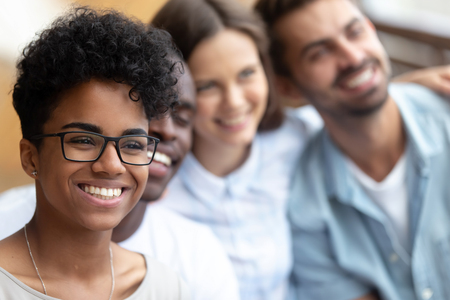 Attractive multiracial millennial people standing in row embracing, close up focus on mixed race girl in glasses with charming sincere smile. Diverse friends spend time together pose smile for picture