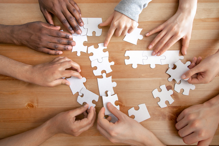 Photo for Close up multiracial people, team assembling puzzle, success teamwork and teambuilding concept, students or colleagues finding best creative solution, decision together, hands top view - Royalty Free Image