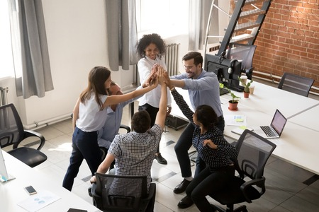 Above top view diverse multiracial millennial colleagues giving high five feels happy and proud achieved goal celebrating successful completion of project expressing support togetherness team spirit.