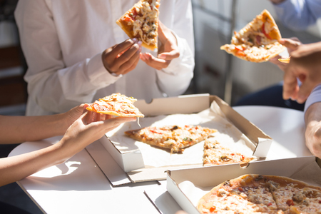 Photo pour Diverse employees colleagues having break enjoy corporate lunch eating pizza in office together, close up hands of business people. Unhealthy fast food at work or delivery take away service concept - image libre de droit
