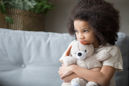 Foto de Upset lonely bullied little african american kid girl holding teddy bear looking away feels abandoned abused, sad alone preschool mixed race child orphan hugging stuffed toy, charity adoption concept - Imagen libre de derechos