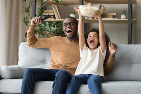 Photo pour Happy overjoyed black family father with kid daughter sport fans watching tv game supporting football team, excited african dad and child girl celebrating victory soccer goal at home sitting on sofa - image libre de droit