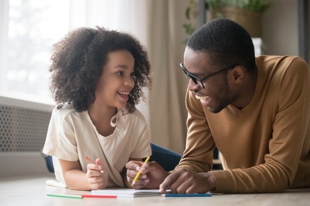 Foto de Cute african american child girl enjoying drawing with colored pencils having fun talking to black dad baby sitter, happy family father and kid daughter laughing play together lying on floor at home - Imagen libre de derechos