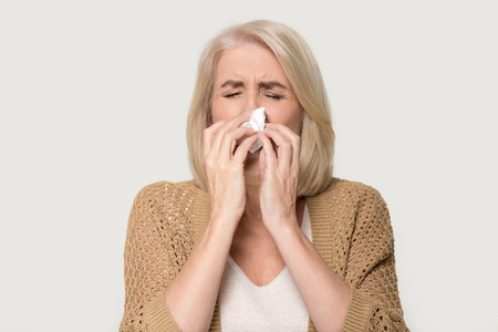 Photo pour Ill allergic old mature woman blowing runny nose got hay fever rhinitis allergy flu, sick middle aged senior lady sneezing in tissue holding handkerchief isolated on white grey studio background - image libre de droit
