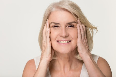 Foto de Happy mature older woman touching face healthy soft moisturized hydrated skin isolated on grey studio background, smiling middle aged senior lady natural beauty treatment anti aging concept, portrait - Imagen libre de derechos
