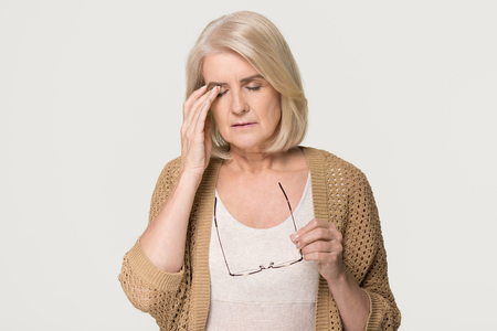Foto de Upset tired old mature woman taking off glasses feeling eyestrain pain, stressed aged senior lady suffer from headache bad vision eye strain fatigue problem isolated on grey white studio background - Imagen libre de derechos
