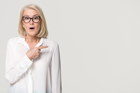 Foto de Surprised old mature businesswoman pointing finger at copy space looking at camera, amazed senior middle aged woman in glasses advertising product service isolated on white grey studio background - Imagen libre de derechos