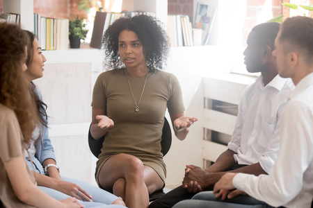 Photo pour African woman psychologist coach speaking at diverse team training or group therapy session, black female trainer counseling addicted people or employees talking sharing problems sitting in circle - image libre de droit