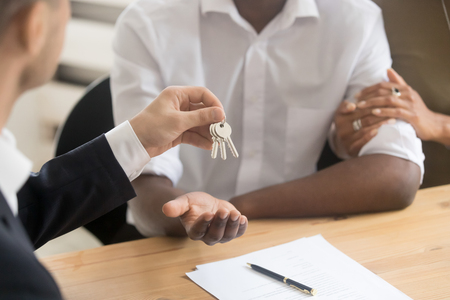 Photo pour Real estate agent realtor holding giving keys to black couple renters tenants, african family customers make deal become first time owners, mortgage, property ownership concept, hands close up view - image libre de droit