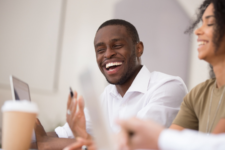 Happy african american businessman laughing talking working together with friendly colleagues, smiling millennial black man having fun team conversation joking with coworkers during office break
