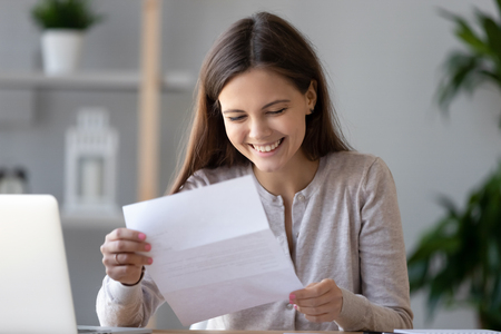 Photo for Smiling happy woman student or worker reading good news in paper letter, sitting at desk with laptop, receive great job offer, success exam results, holding document in hands, great deal - Royalty Free Image