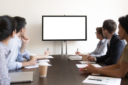 Foto de Business executive people group sitting at conference table looking at white blank mockup tv screen on wall watching presentation in meeting room, company training corporate team seminar in boardroom - Imagen libre de derechos