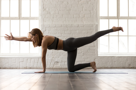 Foto de Attractive woman in grey sportswear, bra and leggings practicing yoga, standing in Bird dog pose, beautiful girl doing Donkey Kick exercise at home or in yoga studio with white walls background - Imagen libre de derechos