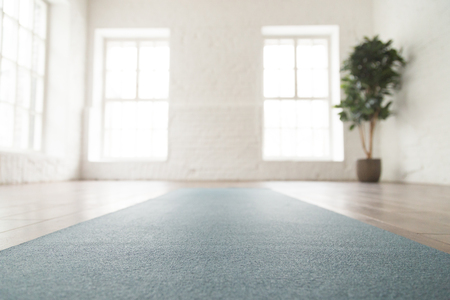 Foto per Close up unrolled yoga mat on wooden floor in empty room, modern yoga studio or fitness center with big windows and white brick walls, sport equipment for meditating or exercises - Immagine Royalty Free