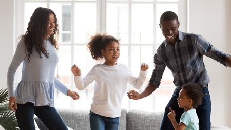 Photo pour Happy young mixed race family of four have fun together in living room, African American mom and dad entertain with little kids, dancing at home, black parents enjoy spending time with small children - image libre de droit