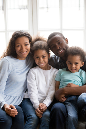Foto de Family portrait of happy young black family sit on couch in living room posing for picture together, smiling African American parents spend time with mixed race relax on sofa at home - Imagen libre de derechos