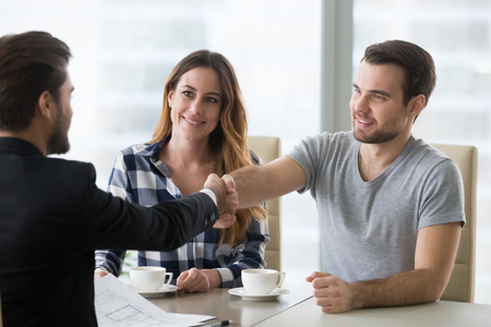 Photo pour Real estate deal concept, happy couple customers handshaking agent or designer at meeting, satisfied property owners and bank broker shake hands, mortgage loan investment, house purchase - image libre de droit
