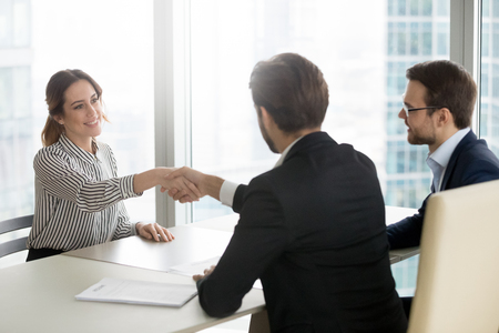 Photo for Confident female job applicant shaking hand of hr recruiting manager employer making good first impression starting interview, recruiters congratulate successful vacancy candidate get hired concept - Royalty Free Image