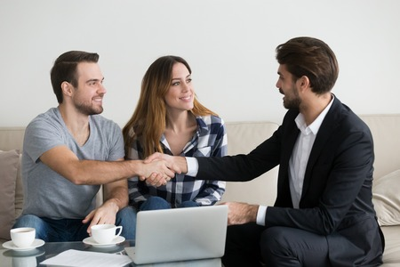 Photo pour Happy family couple renters tenants handshaking landlord at meeting making real estate deal for apartment rent purchase, clients customers and adviser insurer shake hands, mortgage concept - image libre de droit