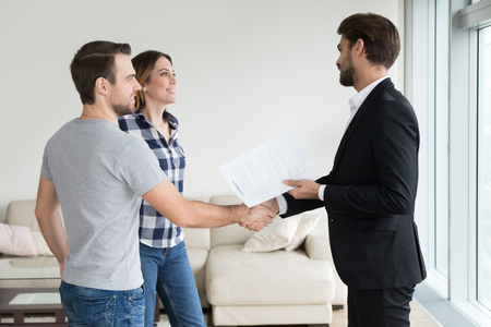 landlord handshaking couple buyers tenants make real estate deal holding rental agreement or sale purchase contract, agent and clients shake hands welcoming renters in new home apartment