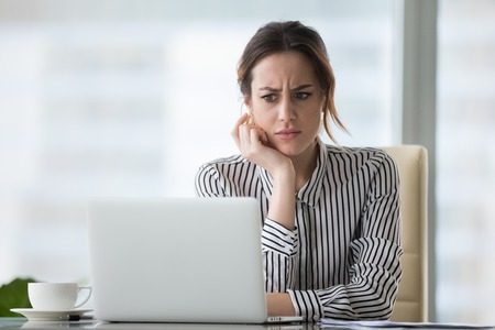 Foto de Confused businesswoman annoyed by online problem, spam email or fake internet news looking at laptop, female office worker feeling shocked about stuck computer, bewildered by scam message or virus - Imagen libre de derechos