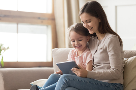 Photo pour Happy family mom and kid daughter using digital tablet sitting on sofa, smiling parent mother with child girl holding pc computer looking at screen do online shopping make video call watch cartoons - image libre de droit