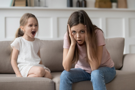 Photo pour Stressed exhausted mother looking at camera feeling desperate about screaming stubborn kid daughter tantrum, upset annoyed mom tired of naughty difficult child girl misbehave yelling for attention - image libre de droit