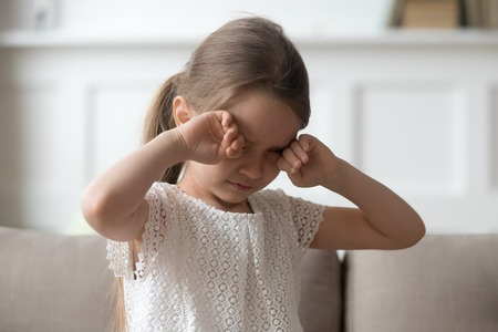 Foto de Sleepy stressed tired upset little child crying rubbing eyes feel abused hurt pain, sad lonely worried preschool kid girl in tears miss parents sitting on sofa alone, unhappy children emotion concept - Imagen libre de derechos