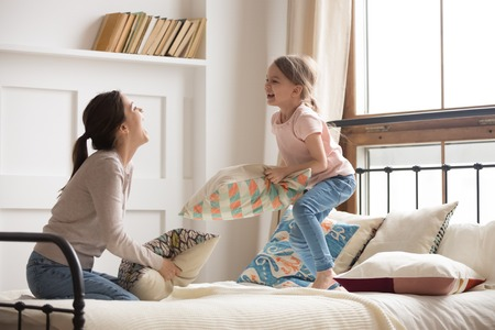 Photo pour Happy mom elder sister and child girl enjoy funny pillow fight on bed, babysitter mother with little kid daughter having fun together in bedroom, cheerful family play laughing together in the morning - image libre de droit