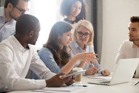 Foto de Young female mentor leader coach teaching employees group analyzing online project explaining business strategy speaking training diverse corporate team with laptop using computer at office meeting. - Imagen libre de derechos
