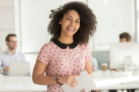 Foto de Happy confident african american business woman employee holding digital tablet looking at camera standing in office, smiling millennial mixed race female intern manager young professional portrait - Imagen libre de derechos