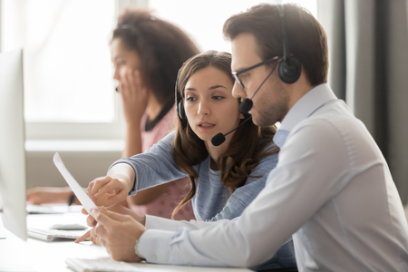 Photo pour Call center service agents operators in wireless headsets discussing papers helping in teamwork at workplace, serious business telemarketers team talking working together in customer helpline office - image libre de droit