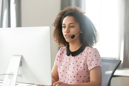 Foto de Serious young african call center operator customer care support manager in wireless headset talking using computer, mixed race telemarketer sales woman consulting client service helpdesk in office - Imagen libre de derechos